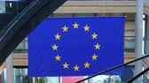 Strasbourg, France - Circa 2018: Zoom out from European Union blue flag with yellow stars hanged over the red carpet and modern staircase inside European Parliament building in Strasbourg, France - di