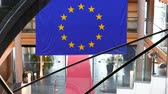 Strasbourg, France - Circa 2018: Slow zoom-out from European Union blue flag with yellow stars hanged over the red carpet and modern staircase inside European Parliament building in Strasbourg, France 動画素材
