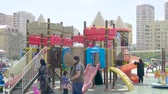 gramado : Baku, Azerbaijan - Circa 2019: Kids having fun at the children slide dedicated children zone in Yasamal Parki green oasis in central Baku surrounded with tall apartment real estate buildings