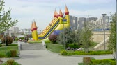 gramado : Baku, Azerbaijan - Circa 2019: Almost empty kids slide dedicated children zone in Yasamal Parki green oasis in central Baku surrounded tall apartment real estate buildings  people resting under tree