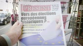 french : Strasbourg, France - May 25, 2019: Man hand POV reading at press kiosk Quotidien Present newspaper featuring 2019 European Parliament election predictions a day before the vote