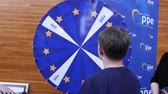 piyango : Strasbourg, France - Circa 2018: European Peoples Party exhibition stand lucky wheel roulette with young boy spinning and winning prize a pencil - European Parliament interior during open day Stok Video