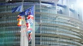 debates : Cinematic sunlight flare over European Parliament headquarter in Strasbourg with all European Union Flags waving in the wind in the Sunday of 2019 European Parliament election slow motion