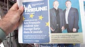 точка зрения : Strasbourg, France - May 27, 2019: Man holding buying La Tribune newspaper front page on street press kiosk newsstand with the results of 2019 European Parliament election and Nexity Business news