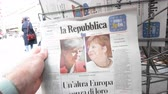 durgunluk : Strasbourg, France - May 27, 2019: Man holding buying newspaper La Repubblica Italian press front page on street press kiosk newsstand with the picture of Theresa May and Angela Merkel
