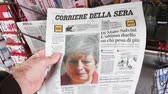 durgunluk : Strasbourg, France - May 27, 2019: Man holding buying newspaper Corriere della sera front page on street press kiosk newsstand with the Theresa May crying announcing resignation Stok Video