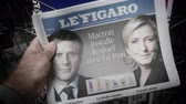 el : Strasbourg, France - May 27, 2019: Man holding buying Le Figaro newspaper front page on street press kiosk newsstand with the results of 2019 European Parliament election Emmanuel Macron and Le Pen on cover Stock mozgókép