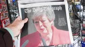 午後 : Strasbourg, France - May 27, 2019: Man holding buying newspaper The Daily Telegraph front page on street press kiosk newsstand with the Theresa May crying announcing resignation 動画素材