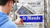 autor : Strasbourg, France - May 25, 2019: Adult French man buying Le Monde at press kiosk newspaper featuring Theresa May and title Spectre of a hard Brexit - slow motion Stock Footage