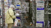 точка зрения : Strasbourg, France - May 25, 2019: Side view of senior woman buying multiple international newspaper at press kiosk featuring 2019 European Parliament election predictions a day before the vote