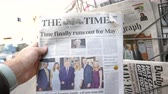 точка зрения : Strasbourg, France - May 25, 2019: Man hand POV reading at press kiosk British The Times latest newspaper featuring Theresa May resignation slow motion city view in background
