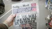 точка зрения : Strasbourg, France - May 25, 2019: Man hand POV reading at press kiosk British Daily Mail latest newspaper featuring Theresa May resignation - you will have a new PM by summer Стоковые видеозаписи