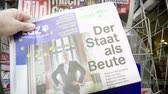 first person view : Strasbourg, France - May 25, 2019: Man hand POV reading TAZ at press kiosk newspaper featuring EU news and title der Staat als Beute Stock Footage