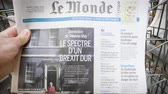 точка зрения : Strasbourg, France - May 25, 2019: Adult French man buying Le Monde at press kiosk newspaper featuring Theresa May and title Spectre of a hard Brexit