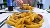 картофель : Close-up view woman eating delicious French fries and traditional Swedish meatballs Kottbullar