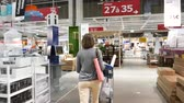 hall : Paris, France - Circa 2019: Rear view of single elegant French woman pushing supermarket cart trolley multiple goods inside IKEA warehouse furniture store shopping for households goods and decorations