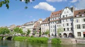pont : Strasbourg, France - Circa 2019: Side view of Strasbourg famous promenade pedestrian street Quai des Bateliers with half timbered houses and people having fun resting on the Ill border on a warm spring day
