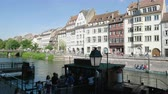 petite france : Strasbourg, France - Circa 2019: Strasbourg famous promenade pedestrian street Quai des Bateliers with half timbered houses and people near Ill river and Batorama Port