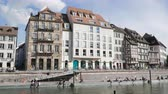 french street : Strasbourg, France - Circa 2019: Strasbourg famous promenade pedestrian street Quai des Bateliers with half timbered houses and people having fun resting on the Ill border on a warm spring day