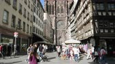 campana : Strasbourg, France - Circa 2019: Tilt up to Notre-Dame de Strasbourg cathedral on a warm sunny day with hundreds of tourists visiting Strasbourg Filmati Stock