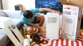 cooling towers : Paris, France - Circa 2019: Young man being helped by his cat unboxing installing new portable air conditioner unit AC during hot summer in his living room inspecting the device Clatronic Stock Footage