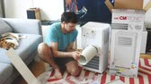 termostat : Paris, France - Circa 2019: Young man being helped by his cat unboxing installing new portable air conditioner unit AC during hot summer in his living room - assembling vent tube - Clatronic CL 3671 Wideo