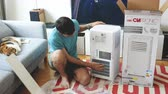 termostat : Paris, France - Circa 2019: Young man being helped by his cat unboxing installing new portable air conditioner unit AC during hot summer in his living room inspection for scratches and bents Wideo