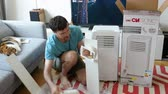 motion timelapse : Paris, France - Circa 2019: Young man being helped by his cat unboxing installing new portable air conditioner unit AC during hot summer in his living room inspection - time lapse fast motion
