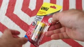 pegajoso : Paris, France - Circa 2019: Man hand POV unboxing unpacking new UHU Sekundenkleber super fast drying glue