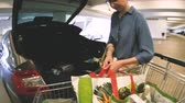 trolejbus : Offenburg, Germany - Circa 2017: Woman arranging heavy bags with groceries from shopping cart inside the car in underground Edeka Supermarket Parking Dostupné videozáznamy