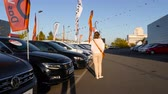 autohaus : Strasbourg, France - Circa 2019: Rear view of young curious woman walking next to black Volkswagen car buy a new car at dealer shop Das Welt - Golf, Passat models