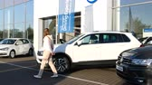 ürünleri : Strasbourg, France - Circa 2019: Rear view of young curious woman walking next to white Volkswagen Tiguan SUV car buy a new car at dealer shop