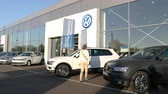autohaus : Strasbourg, France - Circa 2019: Rear view of young curious woman approaching admiring white Volkswagen Tiguan SUV car buy a new car at dealer shop Stock Footage