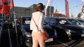 autohaus : Strasbourg, France - Circa 2019: Rear view of young curious woman walking between multiple Volkswagen cars buy a new car at dealer shop Das Welt