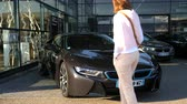 autohaus : Strasbourg, France - Circa 2019: People and curious woman walking next to black BMW i8 electric Premium Selection at German car dealership - front view of the car Stock Footage