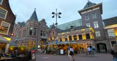 noord holland : Haarlem, Netherlands - Circa 2018: Pedestrians walking at dusk in front of Lange Begijnestraat building with terrace and cafe at the first floor - sightseeing Dutch city