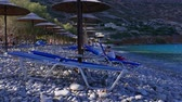 şezlong : Sun beds and umbrellas on gravel beach, Crete