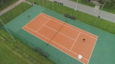 counterclockwise : Senior couple is playing tennis on court in green park. Aerial vertical top view. Drone is flying around Stock Footage