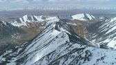 высокий : Snowy Mountains at Sunny Day. Aerial View. Drone is Flying Forward over Mountain Ridge. Camera is Tilting Up. Establishing Shot at High Altitude