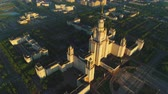 szovjet : Flying over Moscow state university main campus in the sunny summer morning. Aerial view. Drone is orbiting around. High altitude shot Stock mozgókép