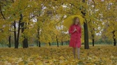 şemsiye : Young lonely beautiful caucasian woman in red coat is walking towards the camera with yellow umbrella in autumn park with yellow fallen leaves. Steadicam full shot