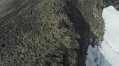 descend : Hiker Man is Hiking and Descending near Cliff in Snowy Mountains of Norway near Cliff using Walking Poles. Aerial View. Drone is Orbiting Around