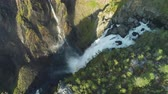 afgrond : Voringfossen Waterfall and Cliffs with Green Trees in Norway at Sunny Summer Day. Aerial View. Drone is Orbiting around Stockvideo