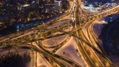 útkereszteződés : Illuminated Road Junction and Cars Traffic at Winter Night. Flyover. Drone is Orbiting. Aerial Hyper Lapse