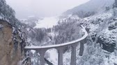 burrone : Landwasser Viaduct with Railway at Winter Snowy Day in Switzerland. Aerial View. Swiss Alps. Snowing. Drone Flies Forward, Camera Tilts Up