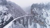 burrone : Landwasser Viaduct with Railroad at Winter Snowy Day in Svizzera. Vista aerea. Alpi svizzere. Nevicando. Drone vola in avanti, la fotocamera si inclina verso l'alto Filmati Stock
