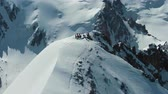 горный хребет : Alpinists on Top of Snow-Capped Mountain in Sunny Day. Aerial View. Drone is Orbiting Clockwise