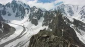 альпинист : Two Climbers on Peak of Rock. Snow-Capped Mountains. Aerial View. Man Makes Dronie