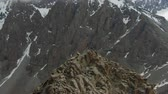 bergsteiger : Two Climbers on Peak of Rock. Snow-Capped Mountains. Aerial View. Drone is Orbiting Stock Footage