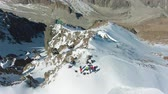 горный хребет : People on Peak of Snowy Mountain in Sunny Day. Aerial View. Drone Flies Forward, Tilt Down